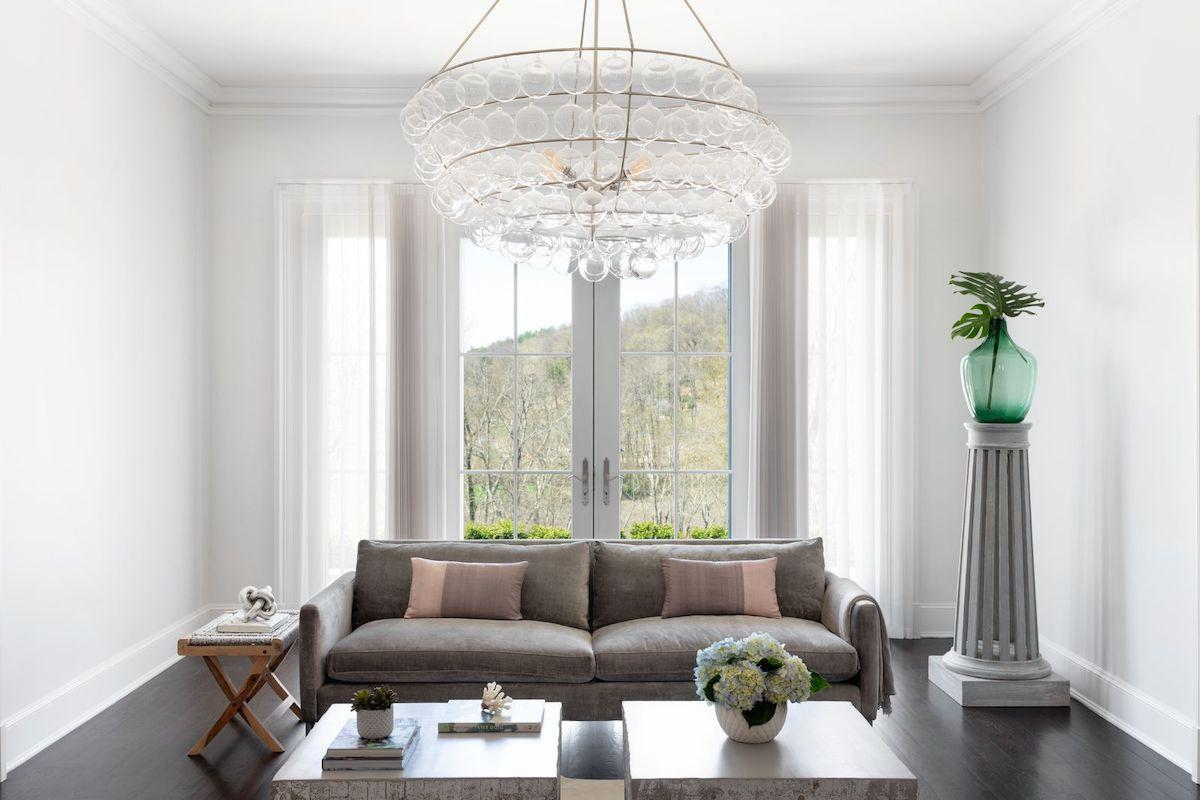 A luxurious living room with huge french doors that have vertical sheers open to each side of the doors