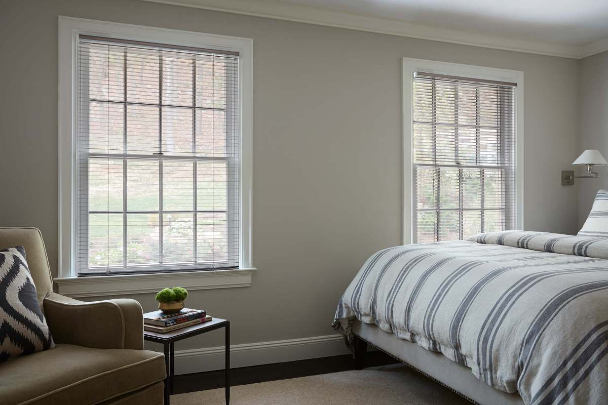 Aluminum blinds cover two windows in a modern bedroom