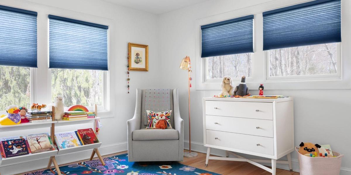 A playful kids room features blue cordless cellular shades on four windows