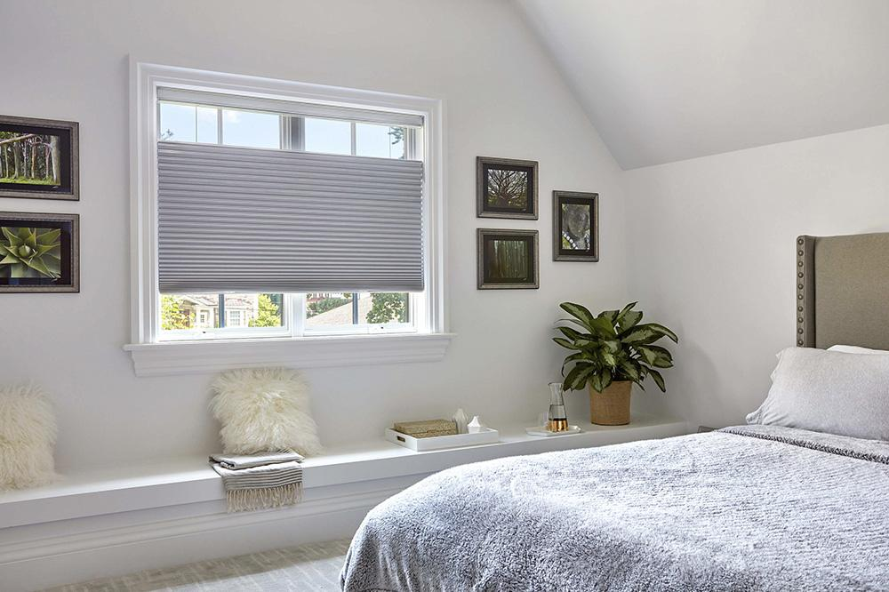 Cellular shades with top-down bottom-up option and blackout material are left partially open on the top and the bottom of the shade