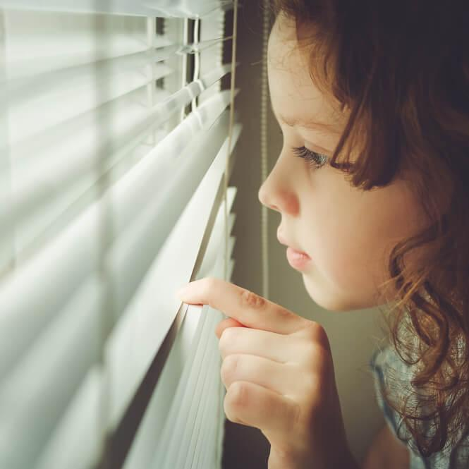 A young girl peers through the slats of horizontal blinds