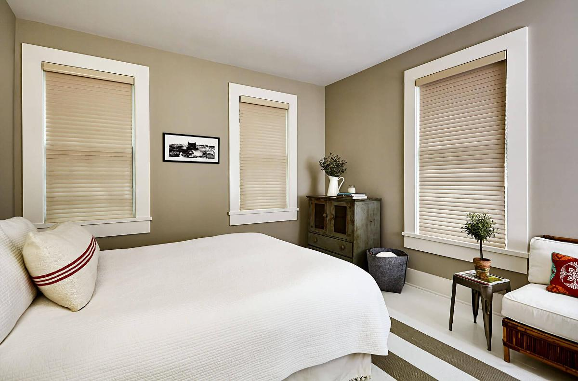 A beautiful modern bedroom has three windows featuring Serenity sheer shades