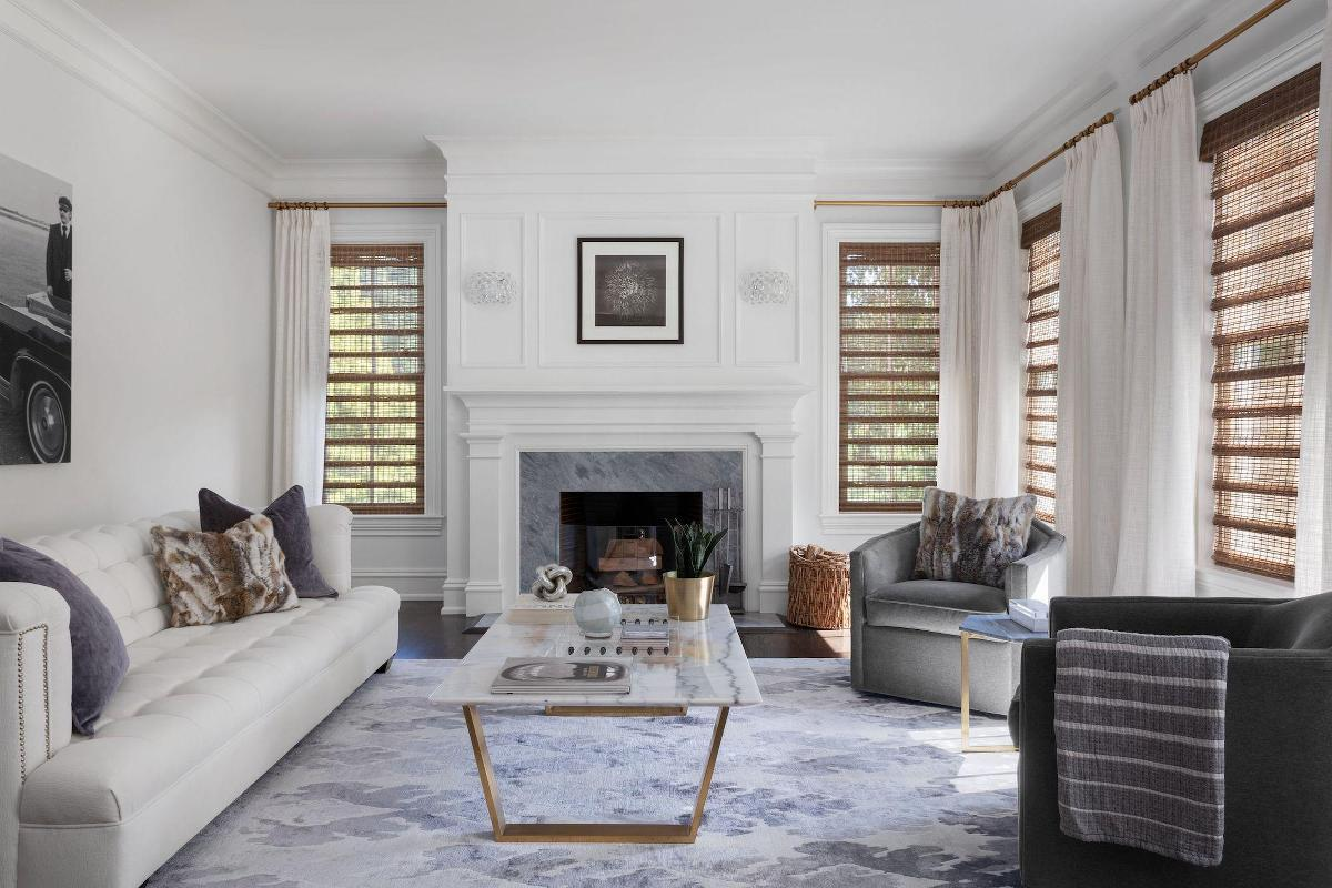 Woven wood shades are paired with drapery in an elegant living room