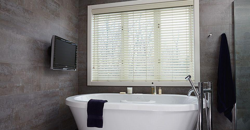 White faux wood blinds in a modern bathroom setting.