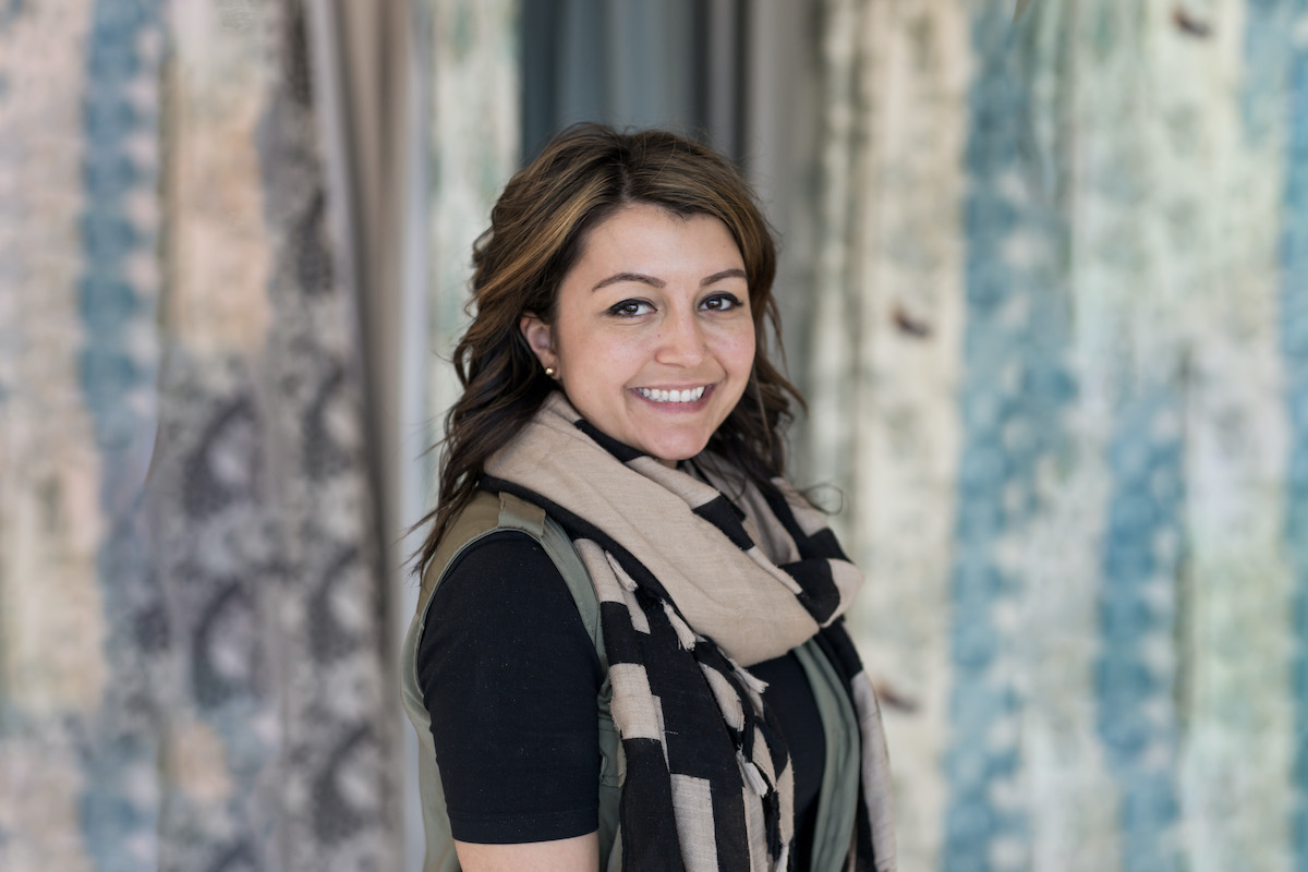 A woman smiles in front of a wall of drapery fabric samples.