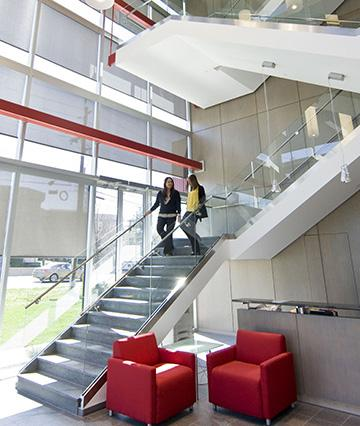 Corporate Office With Two Women Walking Down The Stairs