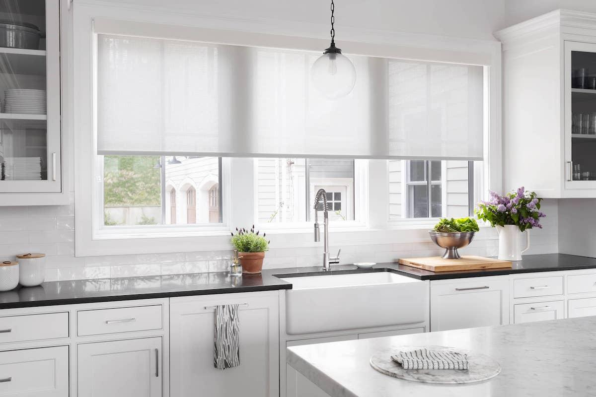 Large kitchen window with white roller shade