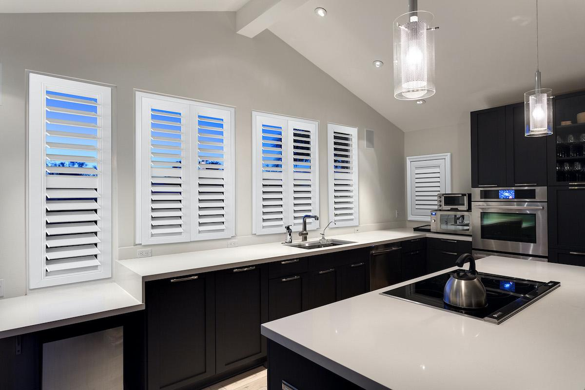 White and black kitchen with white shutters on the inside of the windows