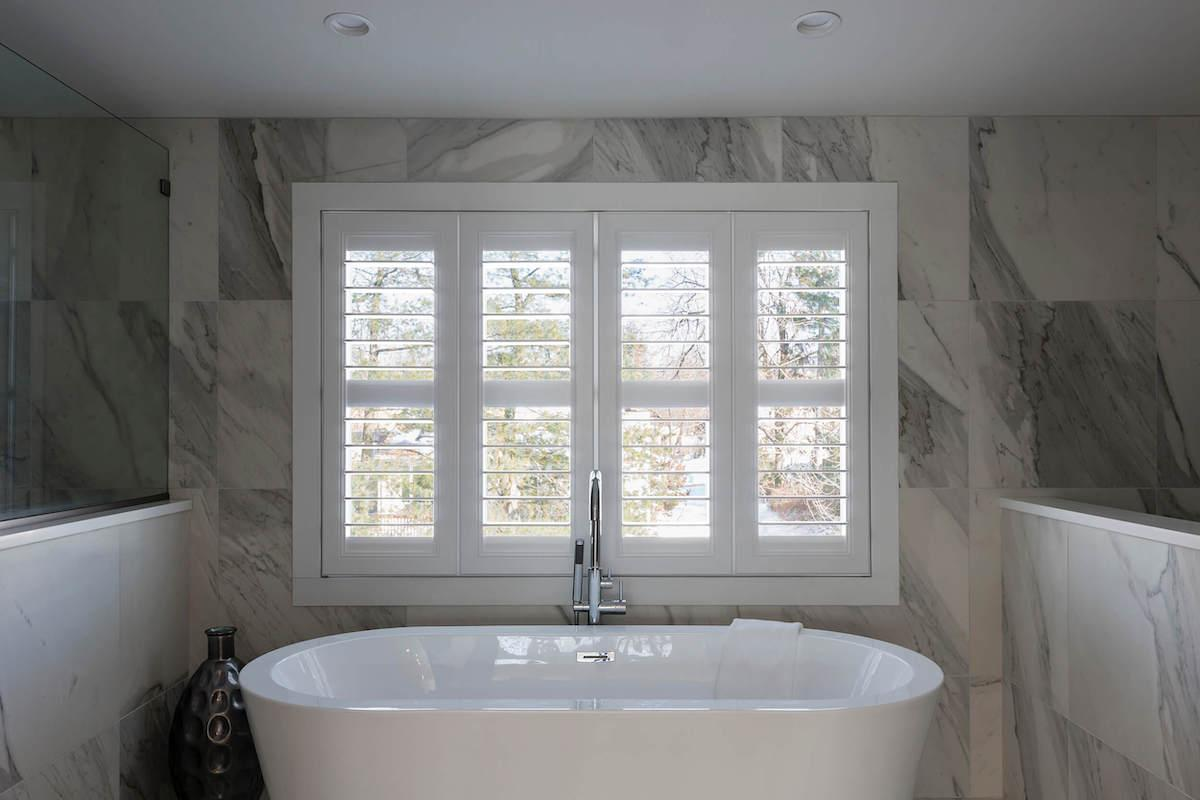 White and marble grey bathroom with large tub and white shutters