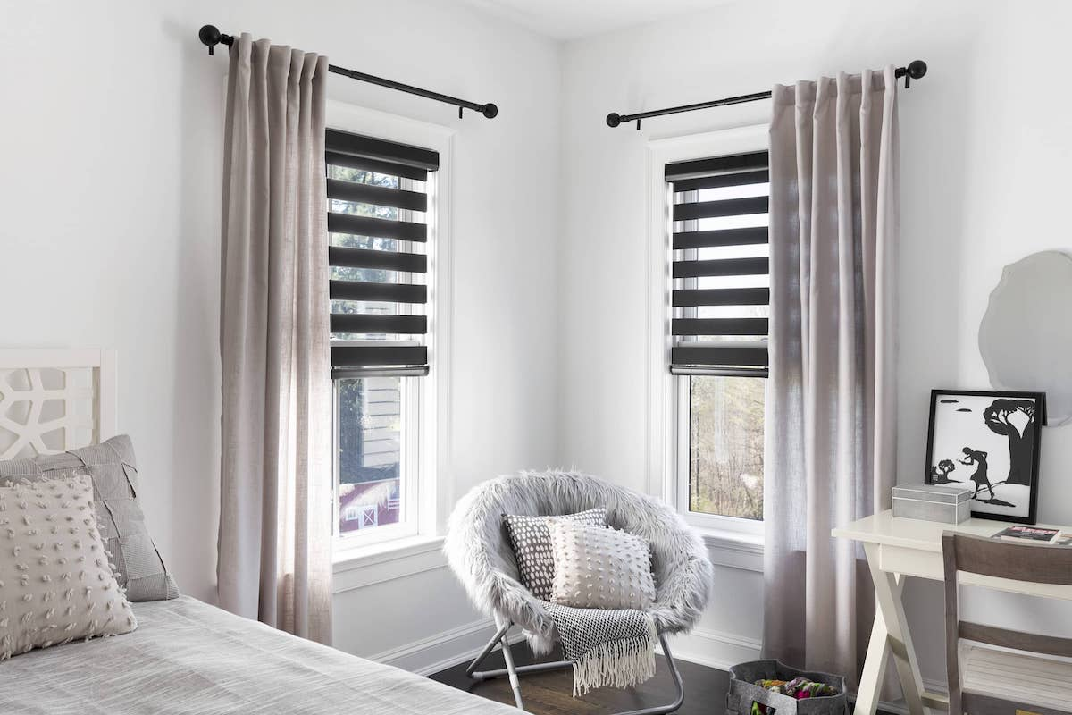 Light bedroom with drapery and dark grey Cascade shades