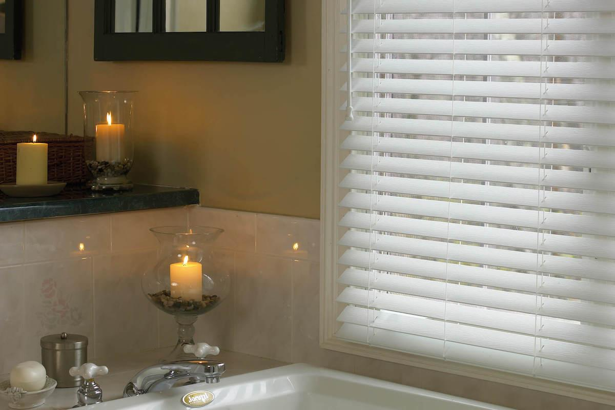White faux wood blinds in a candle-lit bathroom