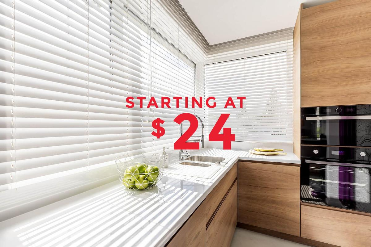 Beautiful faux wood blinds displayed in this modern kitchen.
