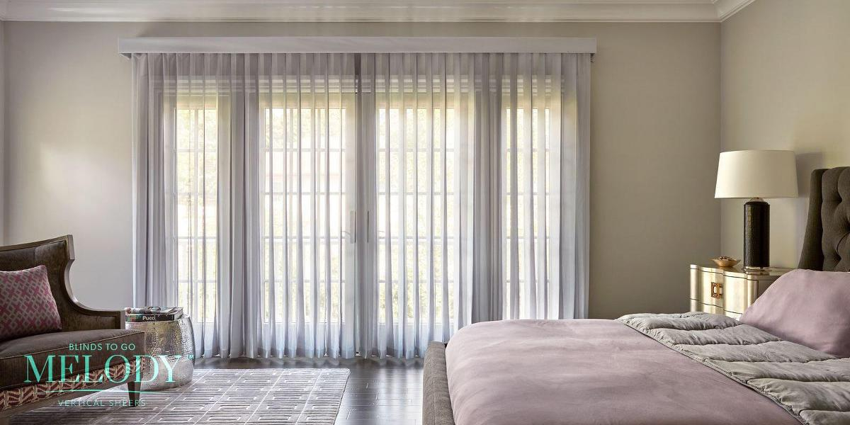 A spacious bedroom features large french doors covered with light grey Melody vertical sheers that allow light to filter in while providing privacy