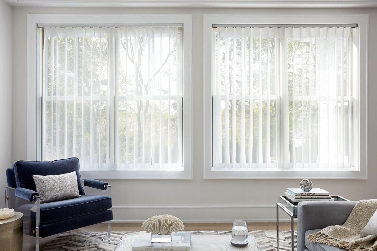 Melody vertical sheers are mounted inside the window frames of two side-by-side windows in a small contemporary living room