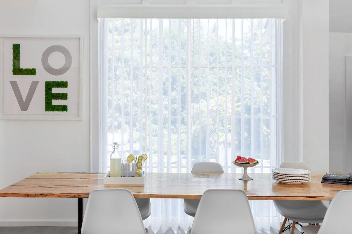 A modern dining room features white Melody sheer shades with a valance on a large window