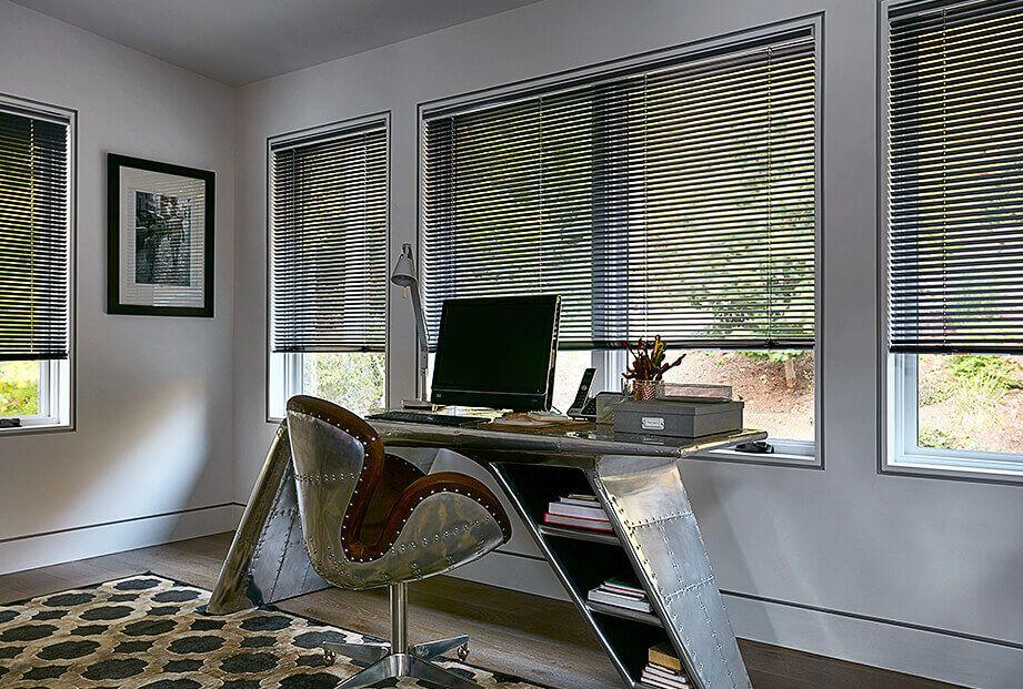 Matte black aluminum blinds in an office with aviator theme desk and chair