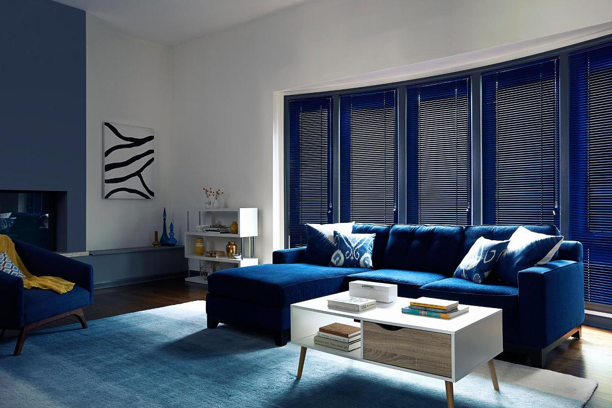 Blue aluminum blinds provides this space a nice contrast against the white wall and works well with the decor.