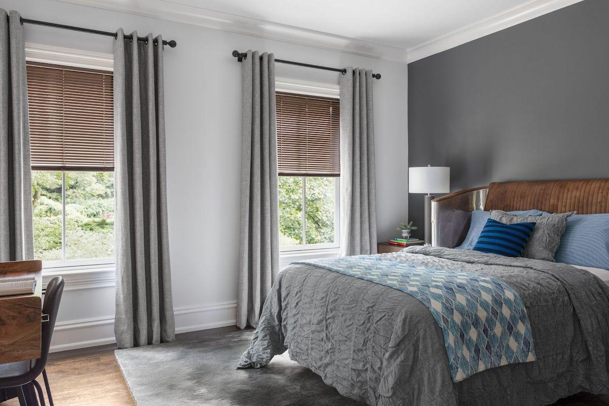 A contemporary bedroom features metallic mini blinds.