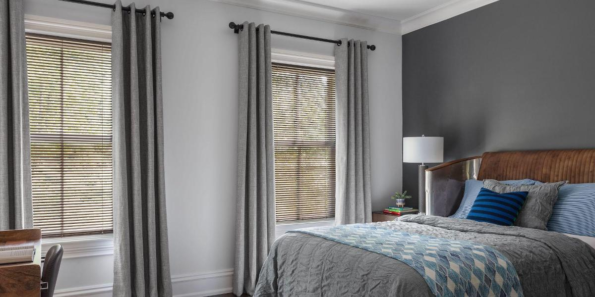 A bedroom features antique copper metallic blinds paired with grey drapery with matte black grommets and curtain rods