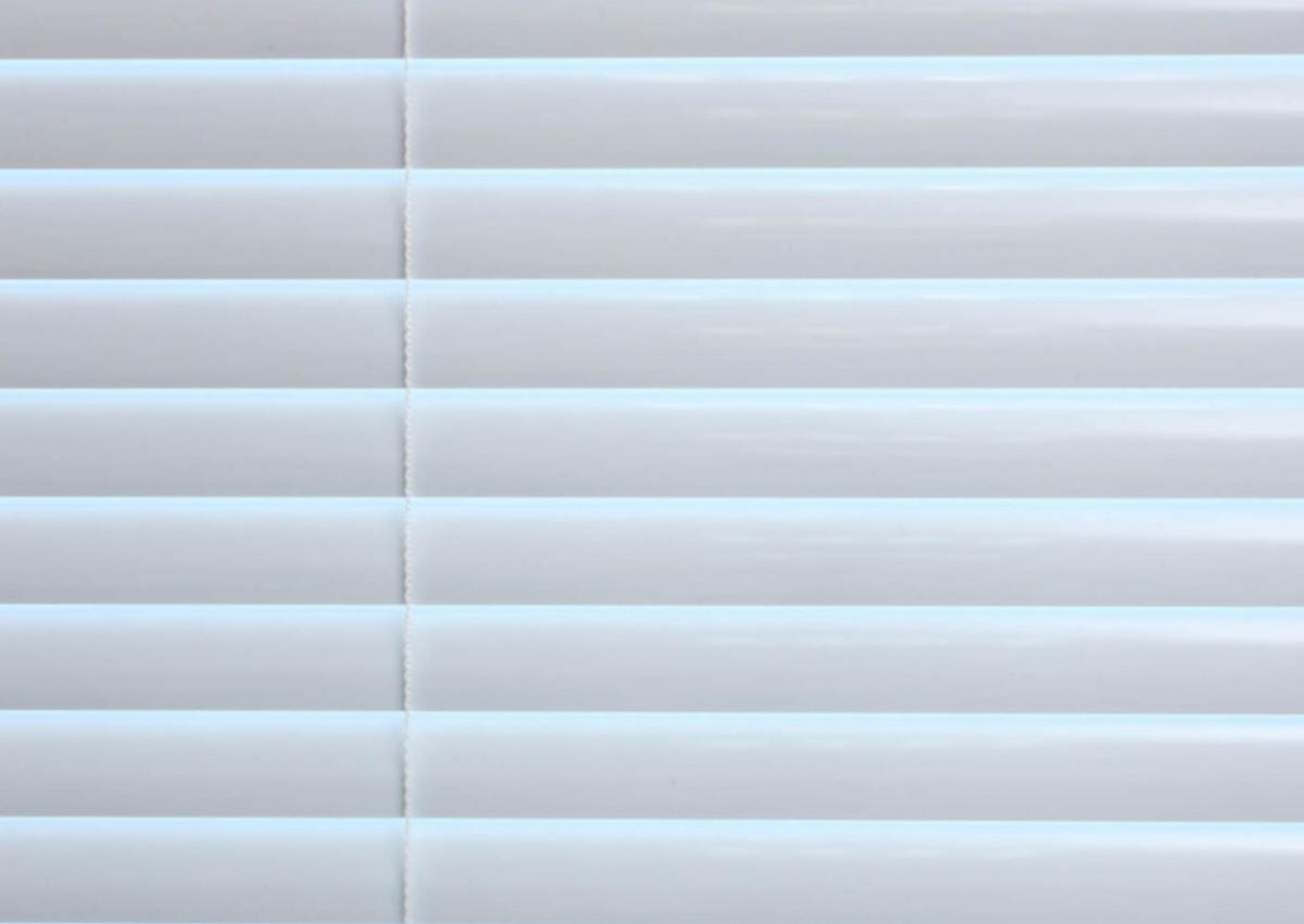 A close up image of mini blinds with no holes in them show the intimacy feature, which eliminates the need for such holes