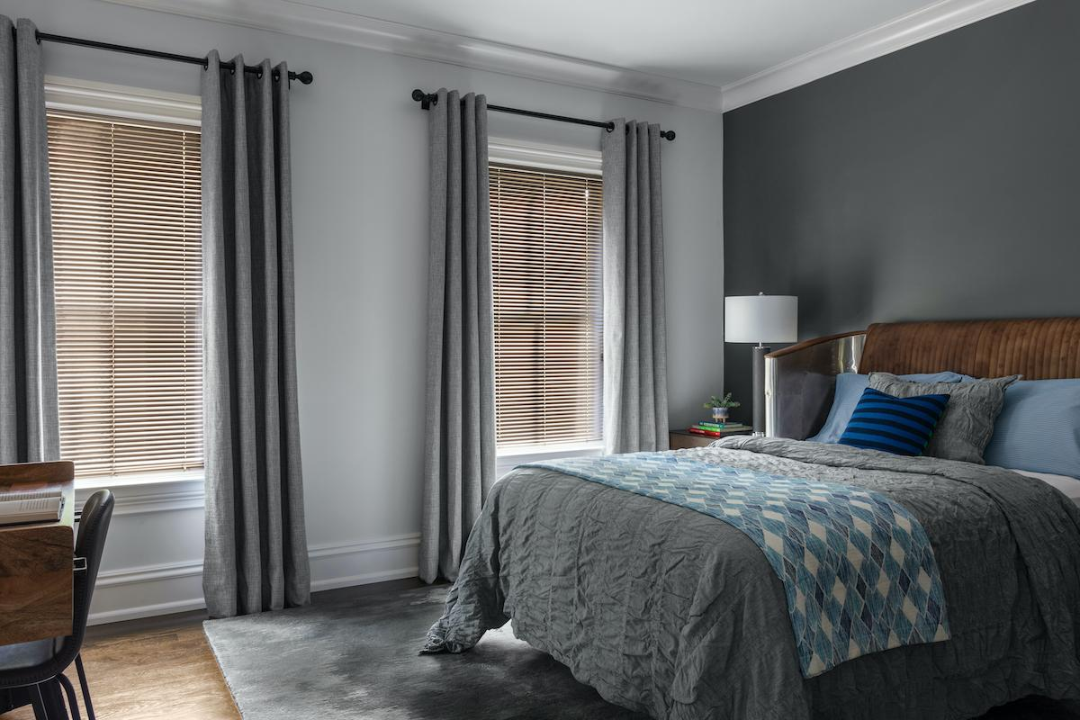Matte gold aluminum blinds are paired with drapery in a contemporary bedroom