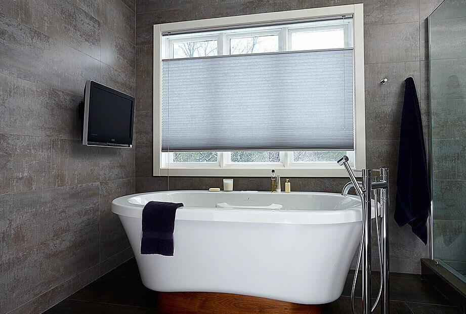 Gray Top-down Bottom-up cellular shades on windows above a beautiful, modern bathtub