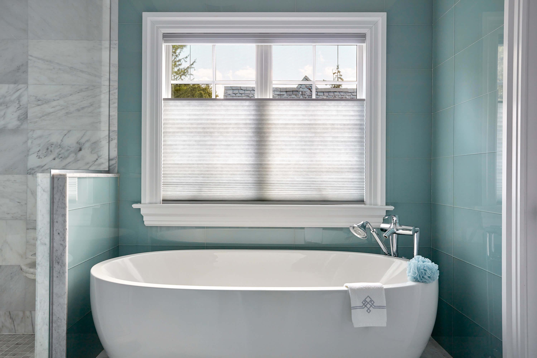Grey Top-down Bottom-up cellular shades on windows above a beautiful, modern bathtub