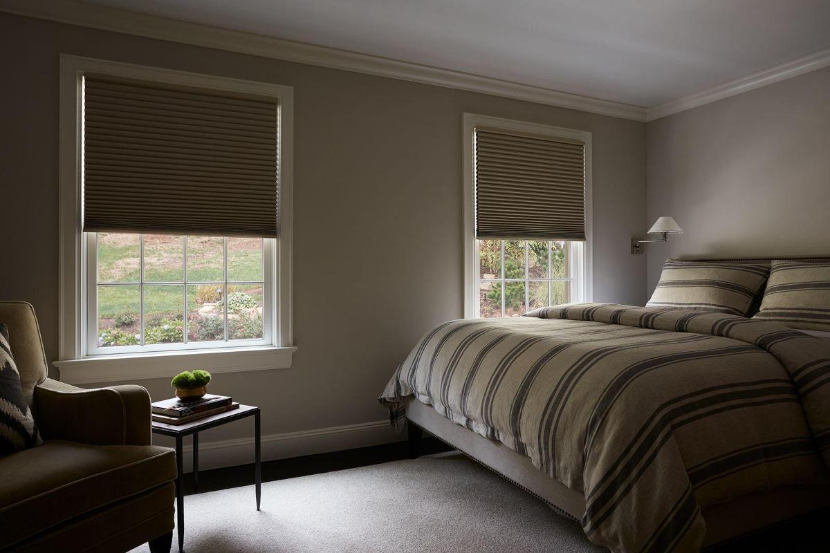 A bedroom features blackout cellular shades