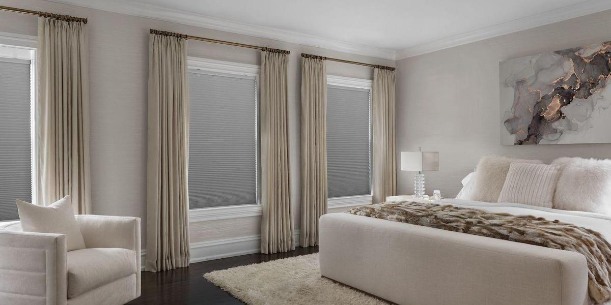 Blackout cellular shades paired with drapery in a contemporary bedroom