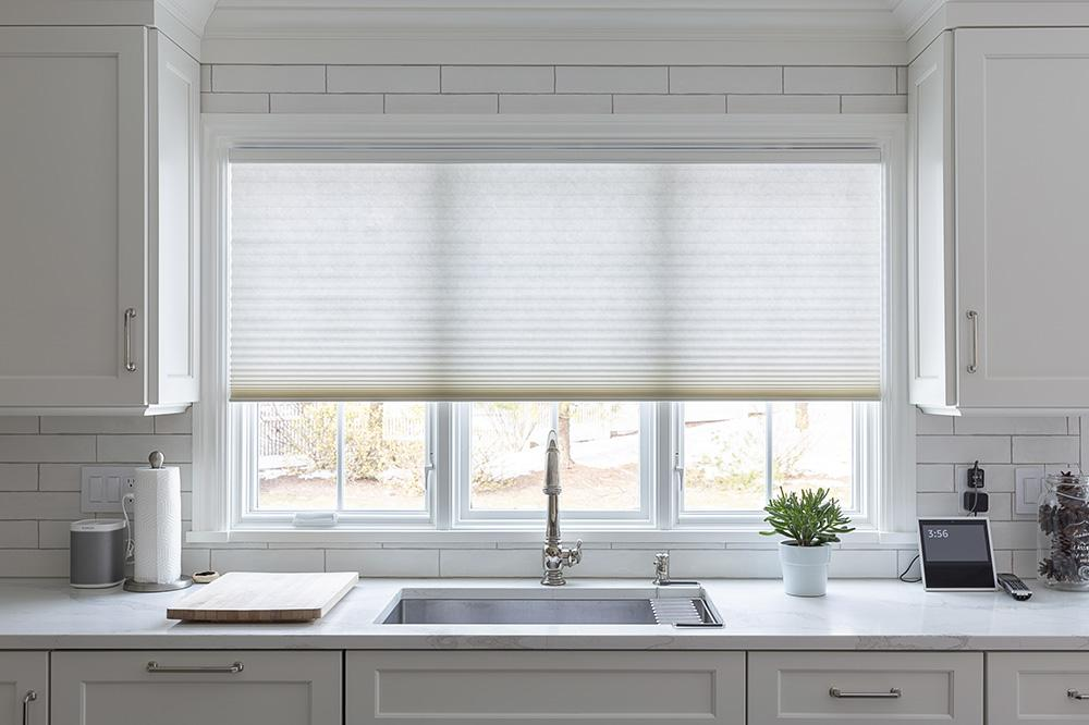 Light filtering cellular shades above the kitchen sink.