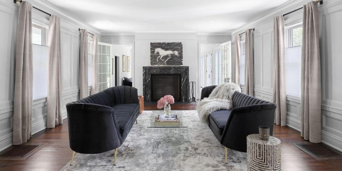 An elegant living room with two couches facing each other has four windows with light-filtering cellular shades that are open at the top and paired with drapery