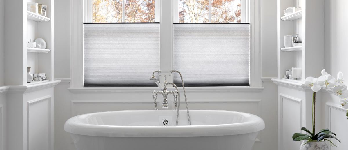 Cellular shades above a bath tub featuring the top down mechanism.