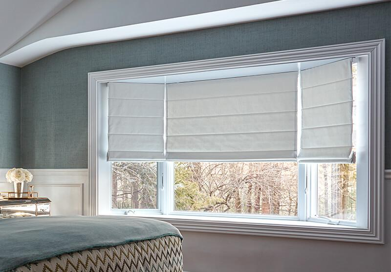 Roman shade with cordless option in a bedroom setting.