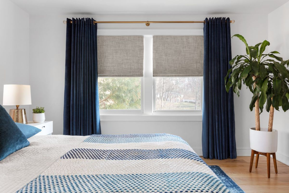Drapes paired with roman shades on a double window in a modern bedroom