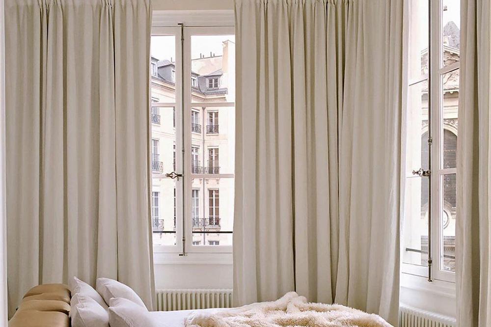 Une chambre à coucher avec plusieurs hautes fenêtres ornées de rideaux de couleur crème