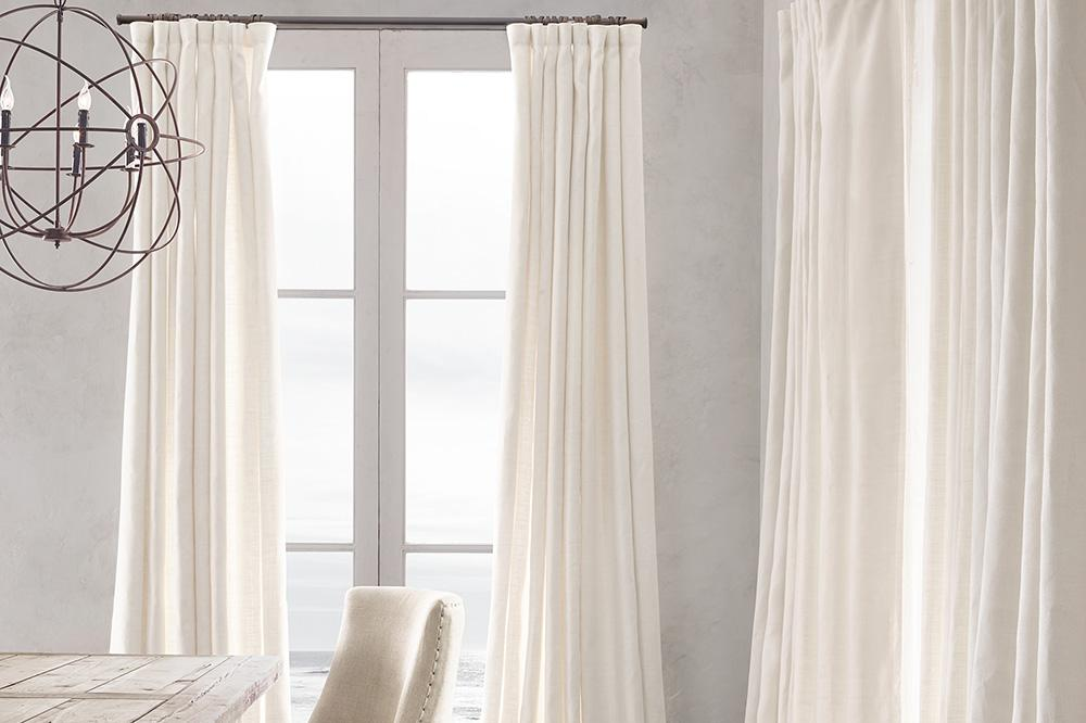 Showcasing drapery in combination with roller shades.