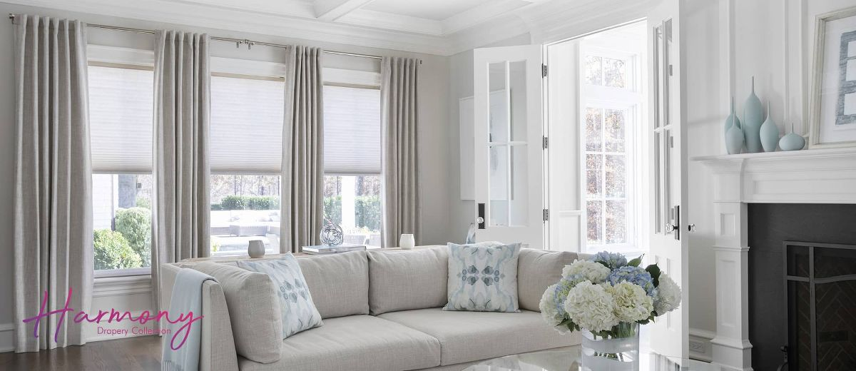 Drapery and cellular shades window treatment combo in a living room.