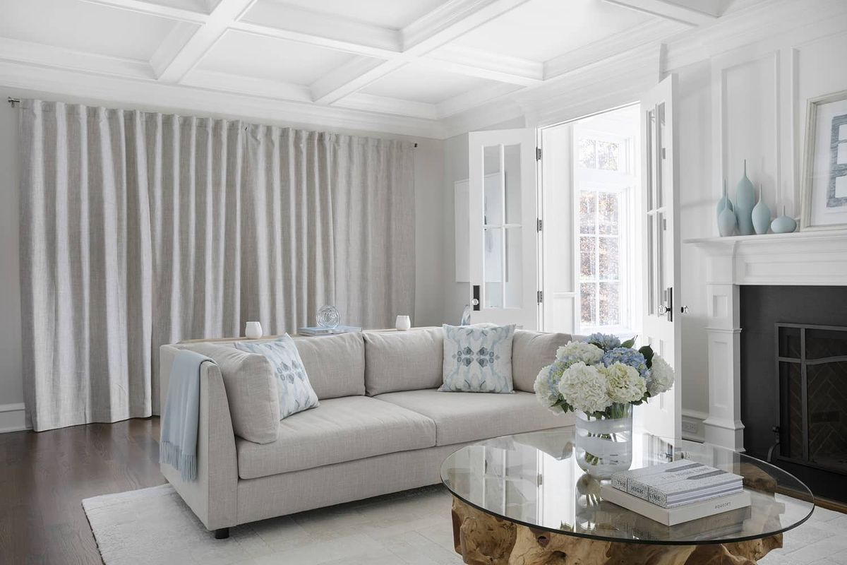 Drapes cover a wall of windows in a beautiful living room