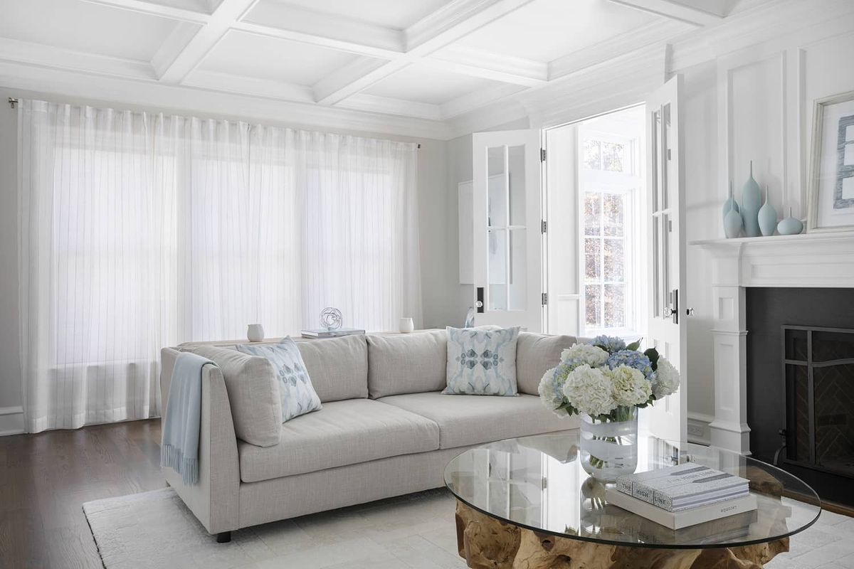 Sheer drapes cover large windows in a bright and modern living room