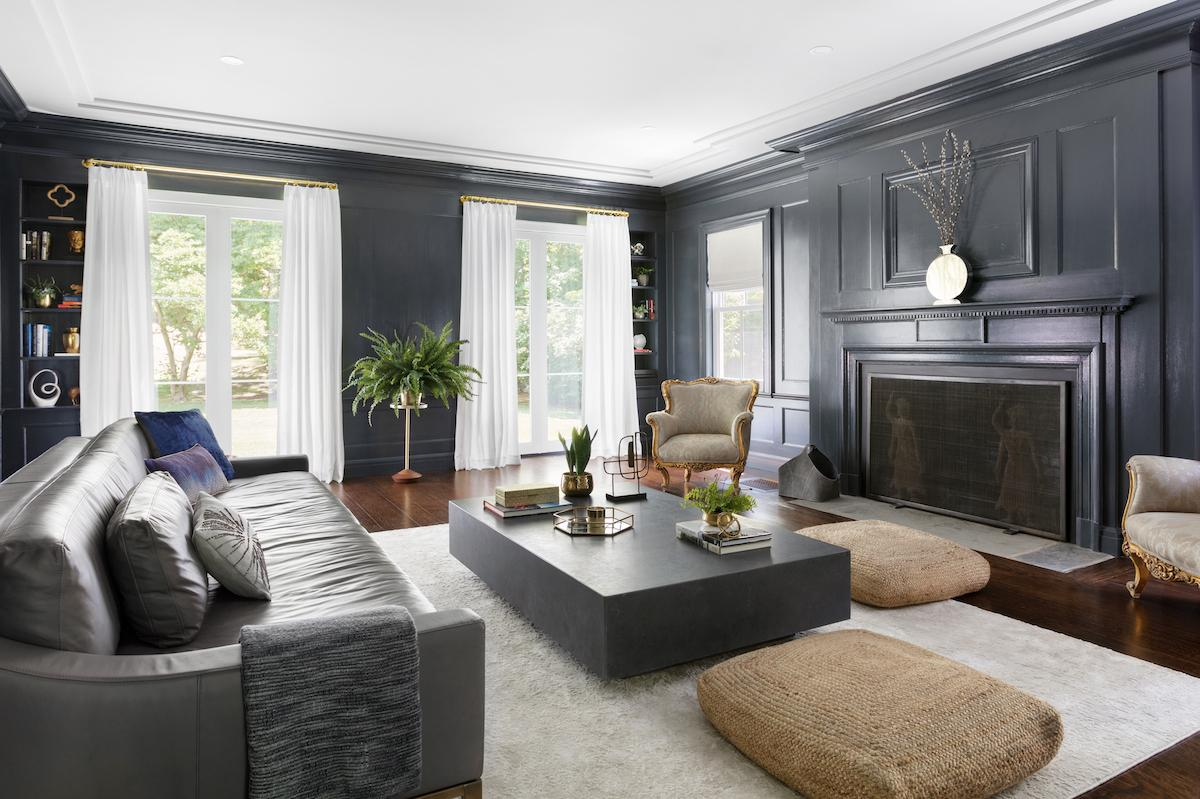 Beatiful white drapes hang from brushed gold rods and rings in a contemporary living room with dark grey walls