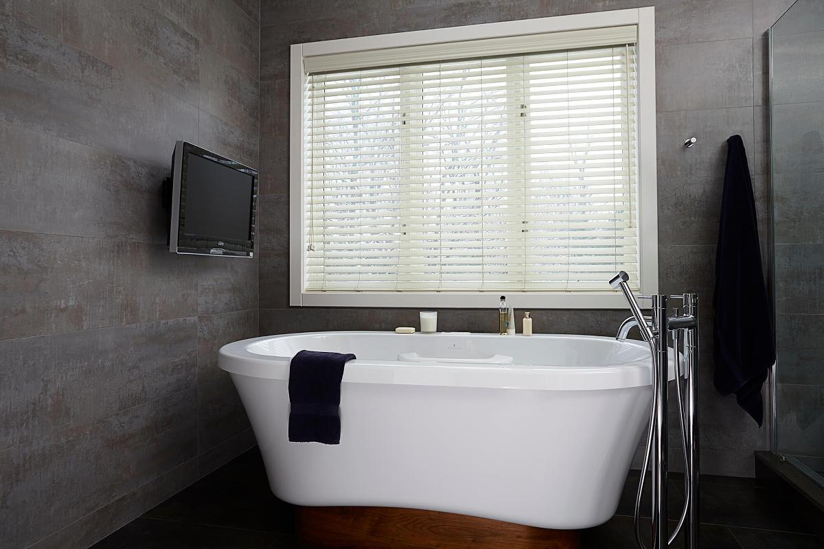 Modern gray bath design with custom white faux wood blind
