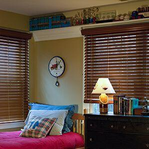 Bedroom featuring faux wood blinds window treatment.