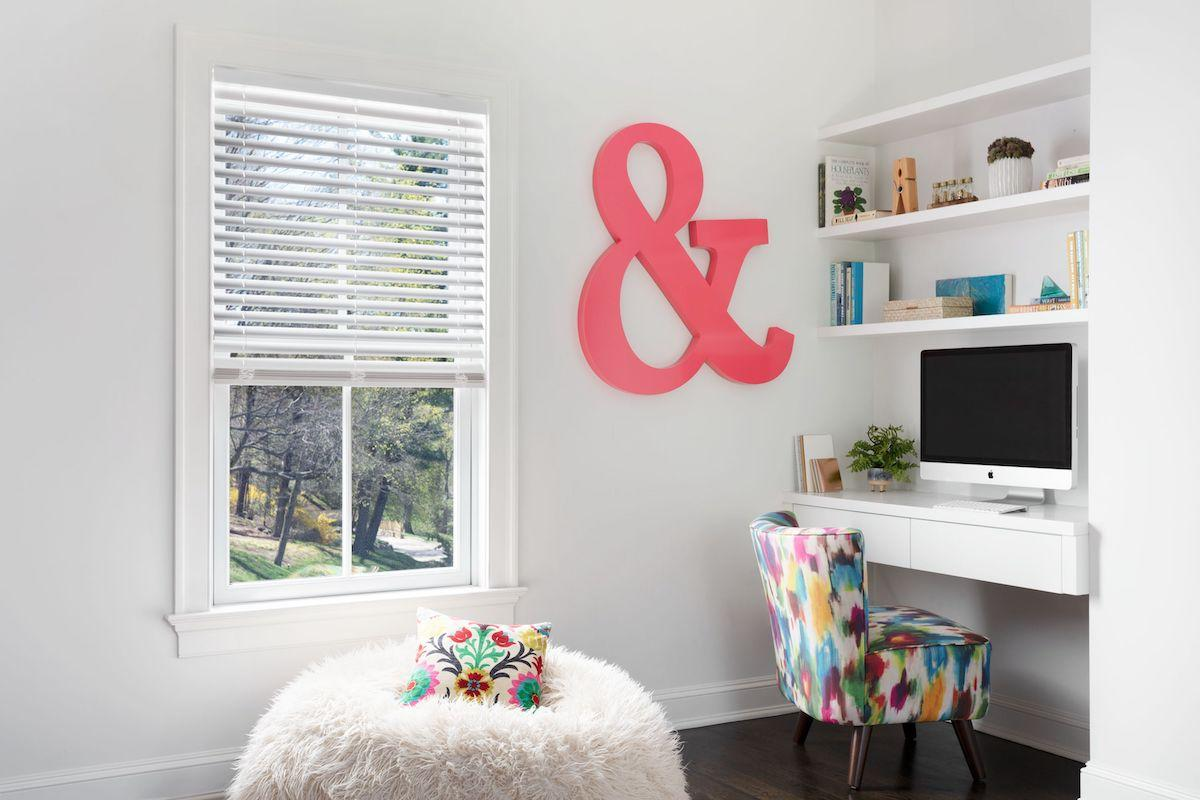 Faux wood blinds allow light in to a modern and playful home office