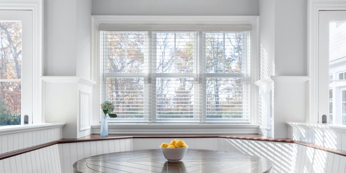 A window featuring white faux wood blinds reveals the view of a spacious yard above large breakfast nook