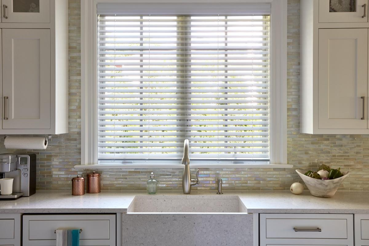 White faux wood blinds cover a window behind a contemporary farmhouse-style sink in a bright, white kitchen