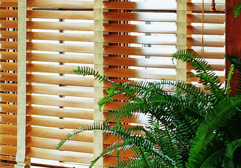 Beautiful light brown real wood blinds with motorized option in a sunroom