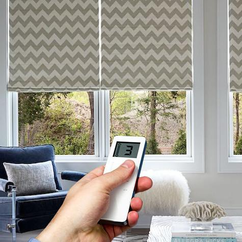 Motorized chevron print roman shades in a sitting room, with a hand holding a remote in the foreground