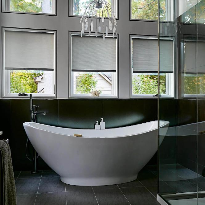 A large contemporary bathtub is situated under three large windows featuring shades that would be difficult to reach, the perfect situation for motorized