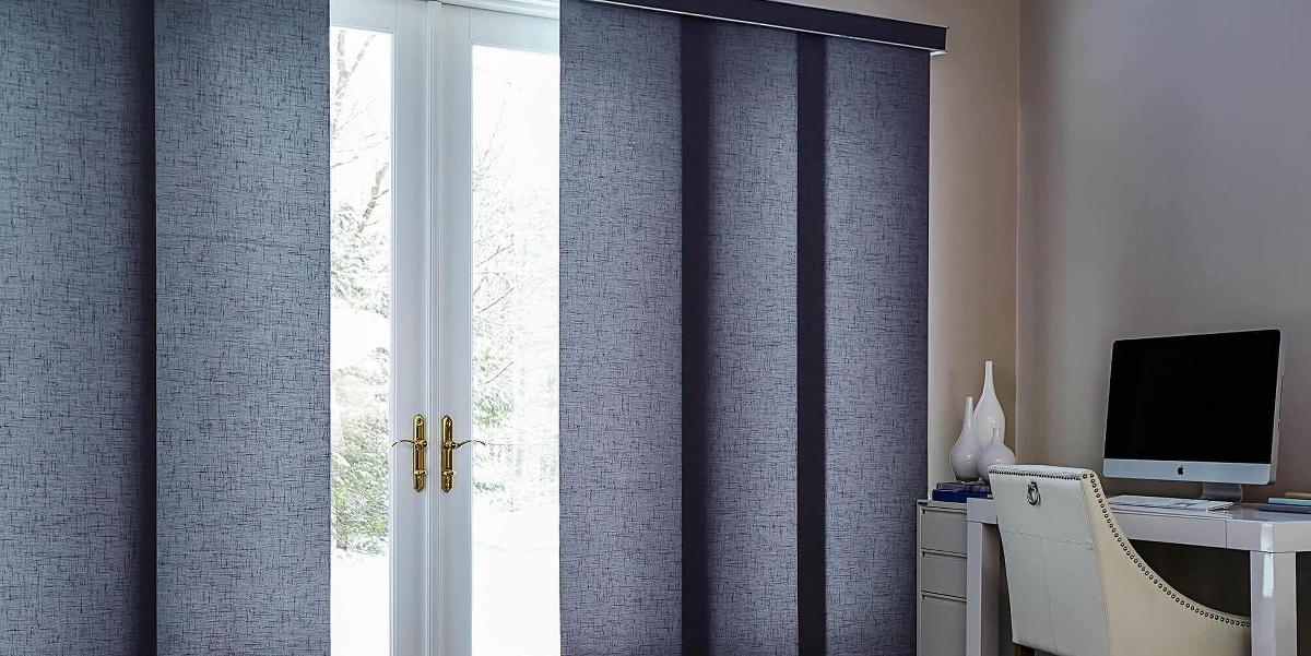 Grey fabric panel track blinds in a home office open in the center allowing a little bit of the view an light from outdoors to come in through a large set of french doors.