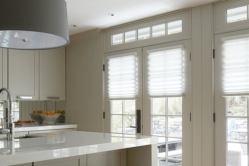 Pleated shades allow light in as they cover the windows on french doors in a kitchen